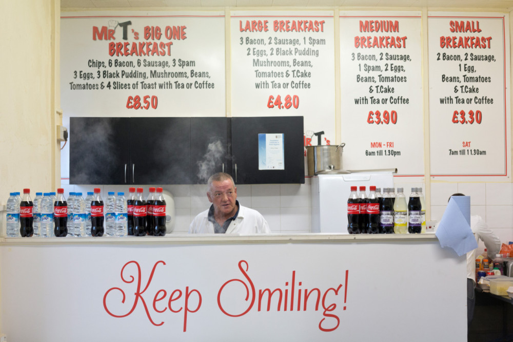 """Jonas Bendiksen. """"Open for Business- At Mr. T's cafe, popular lunch spot for textile mill workers in Dewsbury"""". 2013. Dewsbury, Kirklees, West Yorkshire, England, UK._1280"""